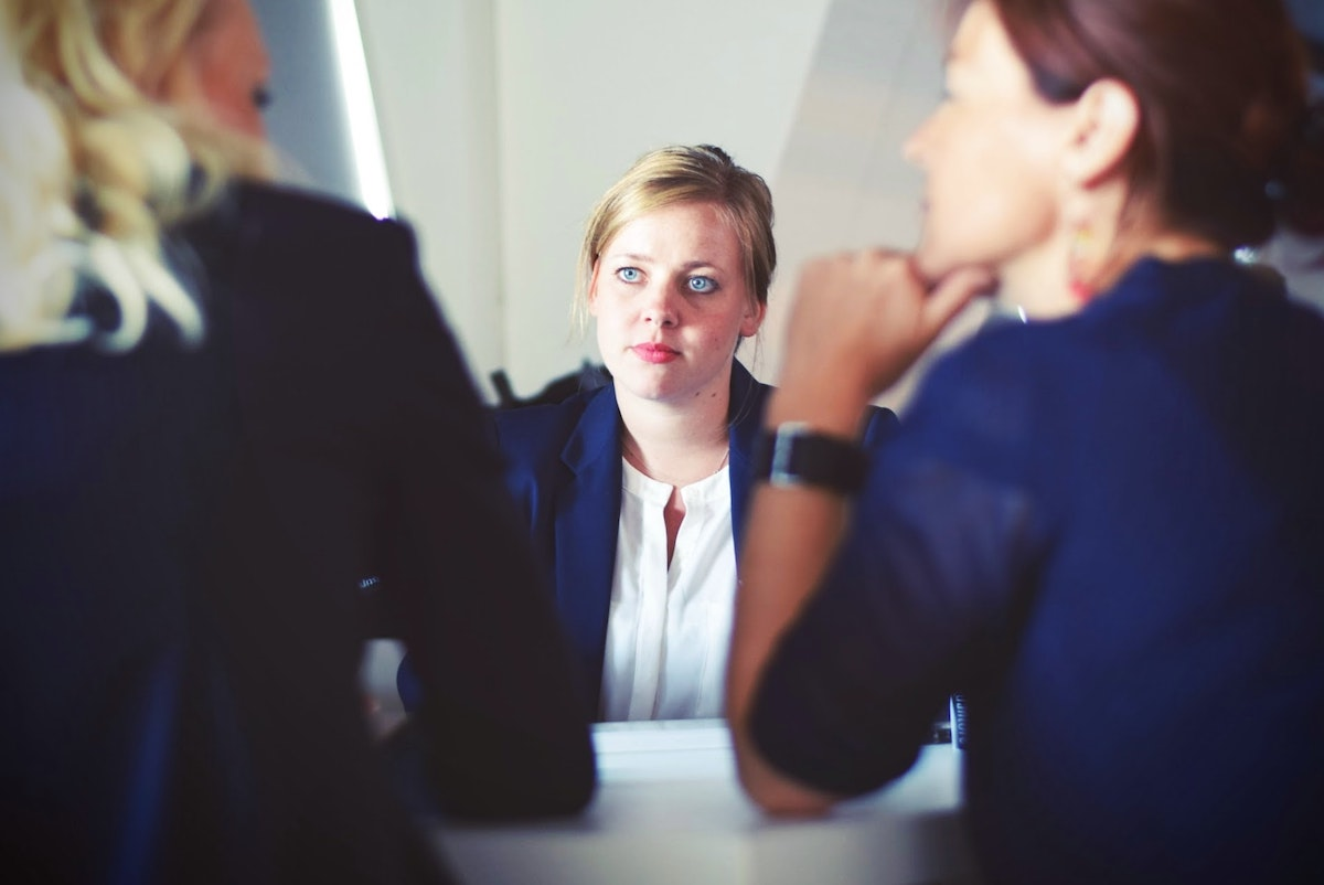 Two female in business attire interviewing a third female job candidate for a project management consultant position