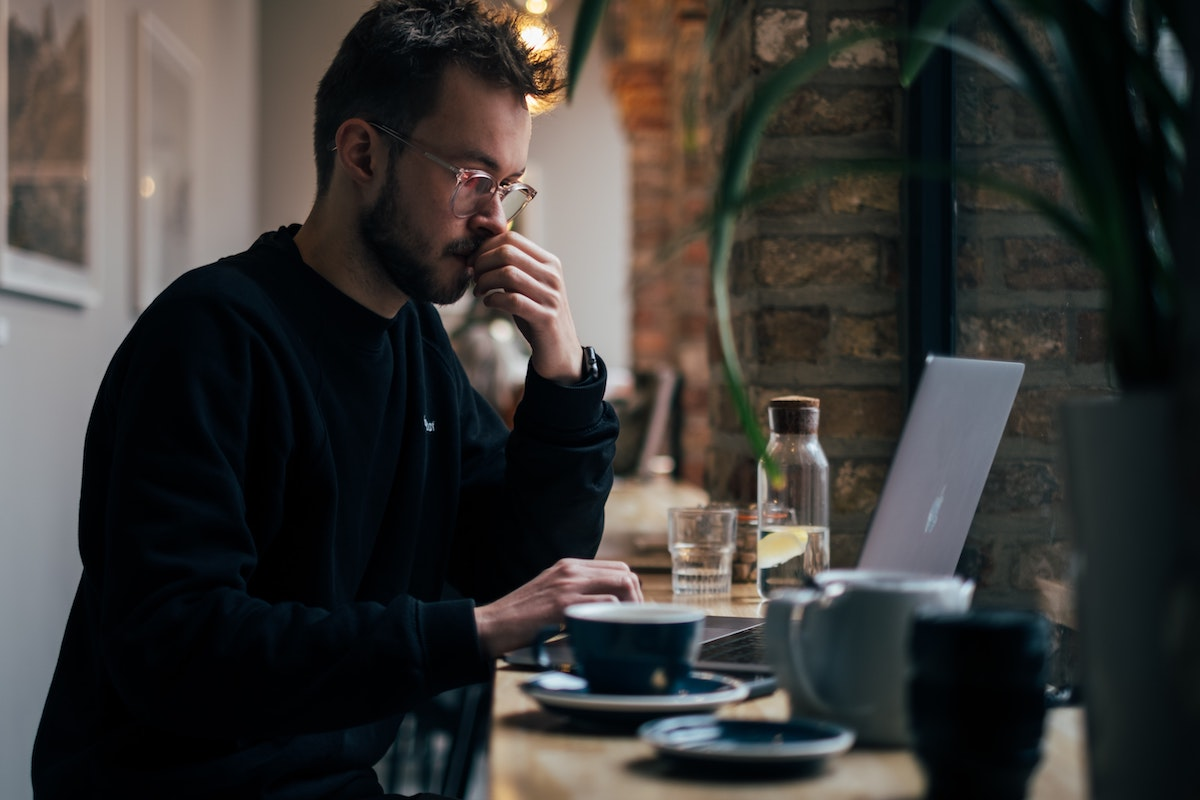 A man thinking deeply in front of his computer while enjoying coffee in a quiet environment